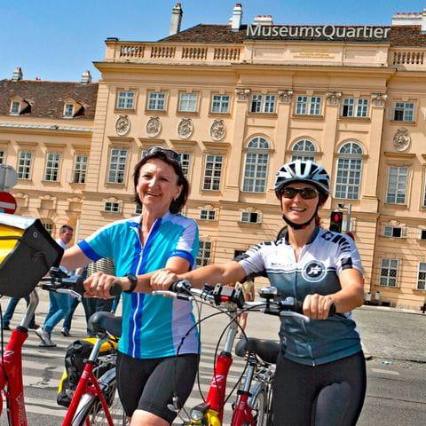 Zwei Radfahrerinnen vor dem Museumsquartier