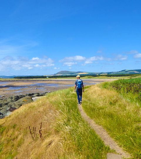 Wanderer bestaunt die malerische Landschaft am Fife Coastal Path