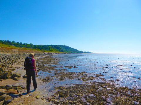 Wanderer genießt den Auslick auf das tiefblaue Meer