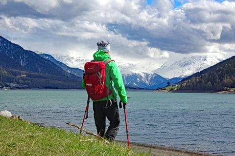 Wanderer am Reschensee mit Blick auf die Dolomiten