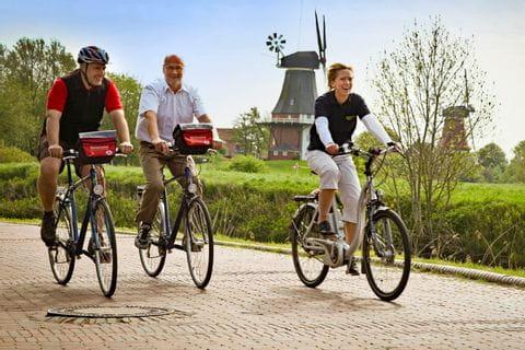 Radfahrer in Greetsiel vorbei an Windmühlen