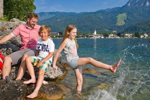 Wandern, Vater mit Kindern beim Spielen im Wasser am Wolfgangsee