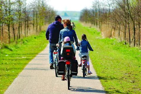 Familie am Radweg in Holland mit Kinderanhänger