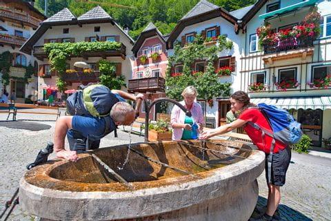 Wanderer erfrischen sich am Dorfbrunnen in Hallstatt