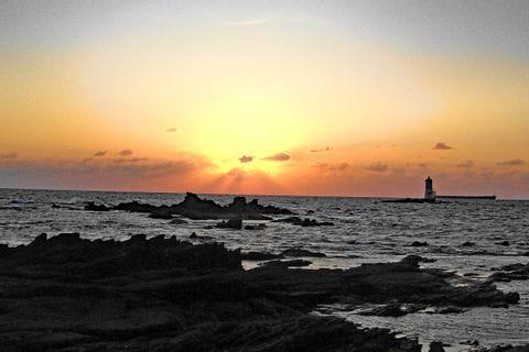 Sonnenuntergang am Meer mit Leuchtturm