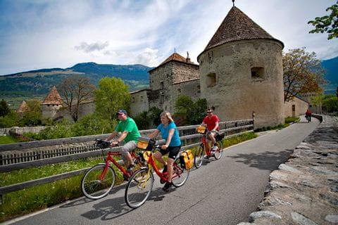 Radfahrer fahren an kleiner Burg vorbei
