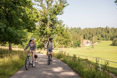 """Schweiz. ganz natuerlich. eBiker Paar unterwegs mit Blick zurueck zum """"Sous la Neuvevie"""" Bauernhof bei Saignelegier."""