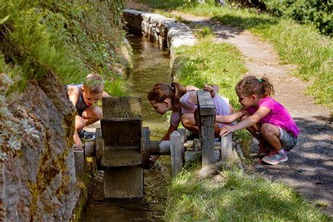 Drei Kinder spielen mit Wasserrad entlang des Wanderweges in Südtirol