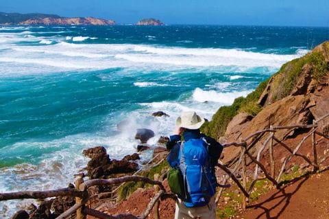 Wanderer mit Panoramablick aufs Meer auf Menorca