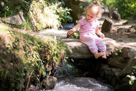 Kleines Mädchen spielt am Wasser eines Waalweges in Südtirol