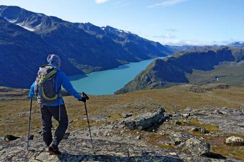 Wanderer genießt die Aussicht auf großen Bergsee und Berge im Nationalpark Jotunheimen