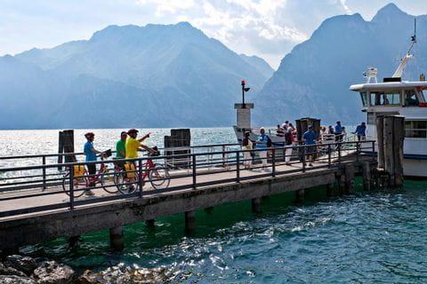 Radfahrer fahren auf die Fähre am Gardasee