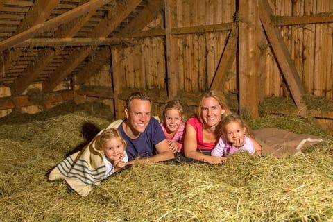 Familie entspannt am Heuboden im Heu
