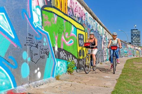 Radfahrer vor der Berliner Mauer
