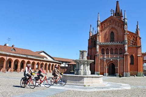 Cyclists passing a fountain in Pollenzo