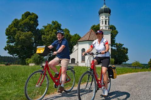Radfahrer vor kleiner Kirche nahe des Riegsees