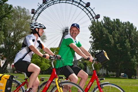 Zwei Radfahrer vor Wiener Riesenrad