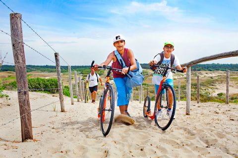 Kinder fahren Fahrrad am Strand im Sand