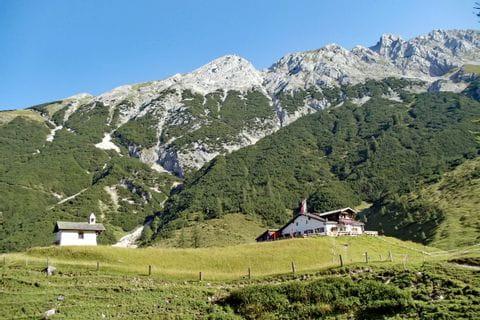 Blick beim Wandern am Tirolerweg auf die Berge und Hütte
