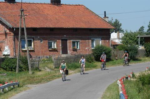 Radler vor einem typischen masurischen Haus