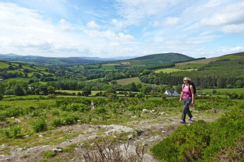 Hiker marvels the lush green landscape of Ireland