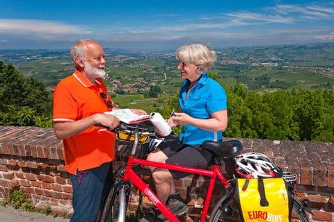 Zwei Radfahrer sitzen auf einer kleinen Mauer