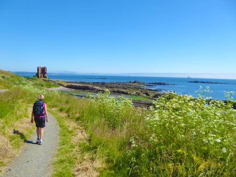Panoramablick am Küstenwanderweg mit Wanderin