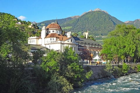 Hiking along river Passer with view to the Kurhaus of Merano
