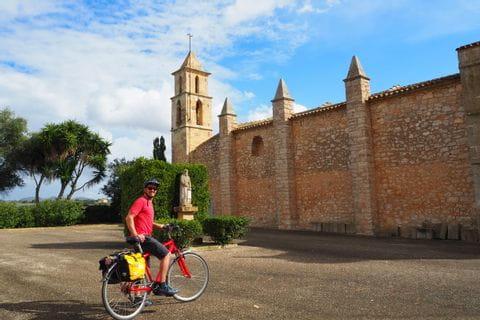 Radfahrer vor der Kirche von Son Negre