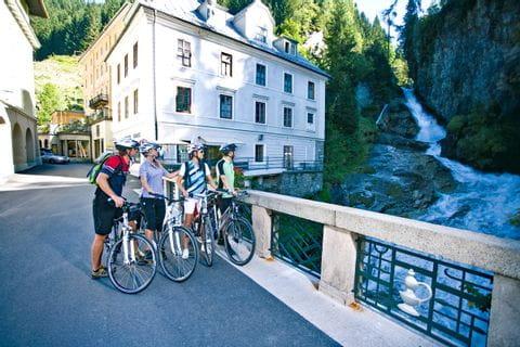 Radler stehen auf Brücke und betrachten kleinen Wasserfall