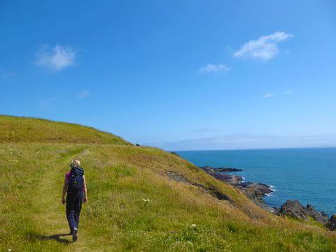 Wanderin genießt die Wanderung entlang der schottischen Küstenlandschaft