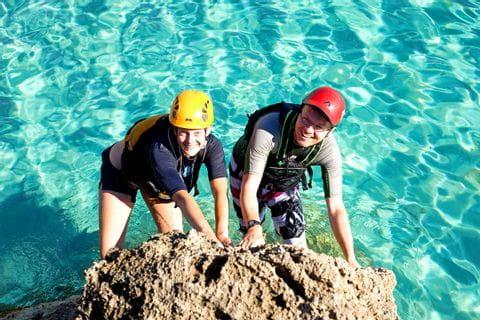 Festhalten am Felsen beim Seacaving in Mallorca