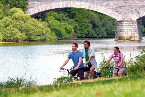 Radfahrer an der Lahn mit Brücke im Hintergrund