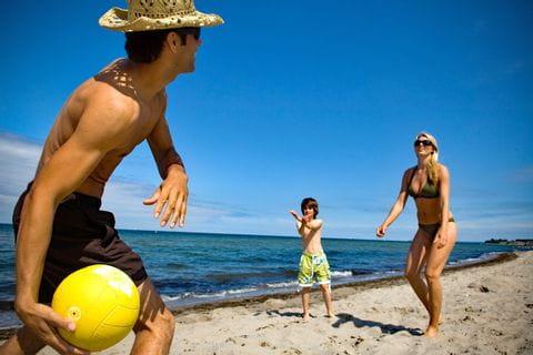 Eltern und Kind spielen Beachvolleyball am Timmendorfer Strand