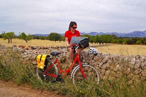 Radfahrerin sitzt auf Steinmauer