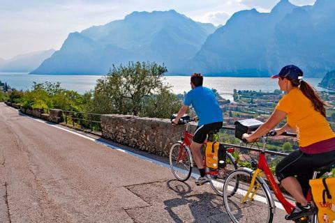 Radler auf Radweg über Torbole mit Blick auf den Gardasee