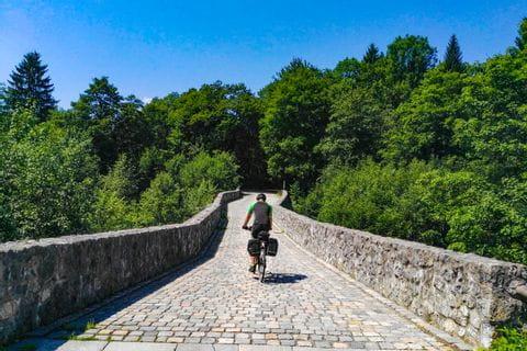 Radfahrer auf einer Steinbrücke