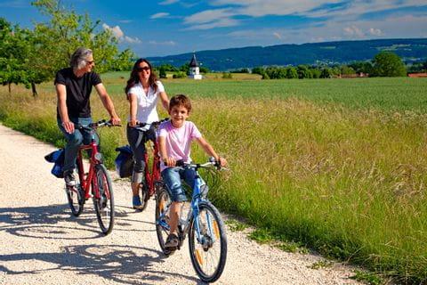 Familie radelt am Bodenseeradweg in der Landschaft