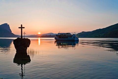Schiff und Kreuz auf Stein bei Sonnenuntergang am Mondsee