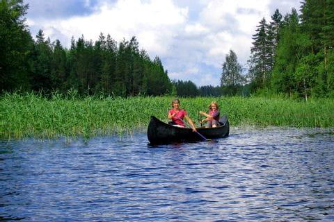 Damen paddeln im Kanu auf der Finnischen Seenplatte