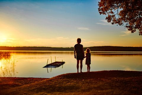Mutter mit Tochter Hand in Hand im Abendrot am See in Schweden