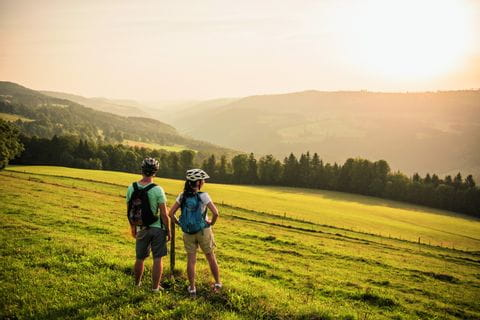 Schweiz. ganz natuerlich. eBiker Paar geniesst die Abendstimmung bei Montmelon.