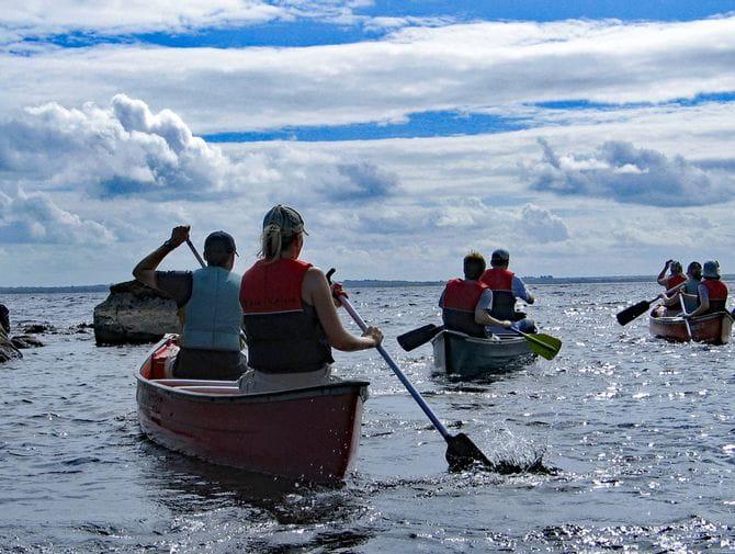 Kanutengruppe paddelt auf See in Irland
